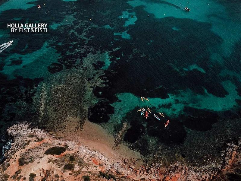 Вид с коптера на бухту острова Mallorca в Испании. Каноэ в бирюзовой воде