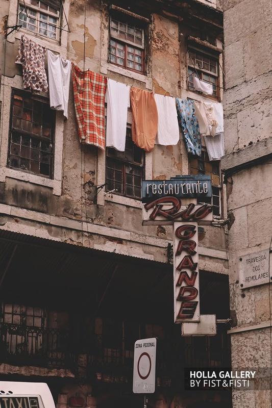 Узкая улица Лиссабона с вывеской и бельем из окна.
