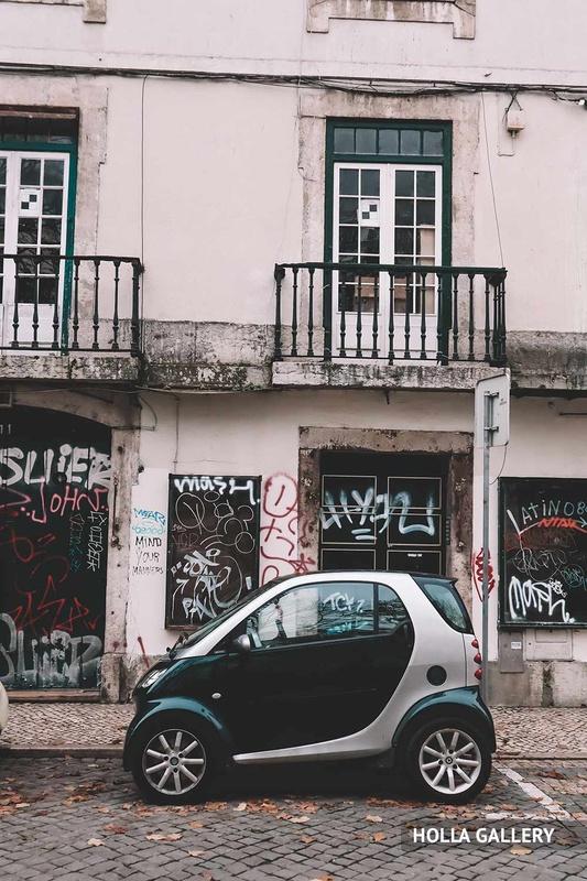 Черная машина у стены с граффити в Лиссабоне