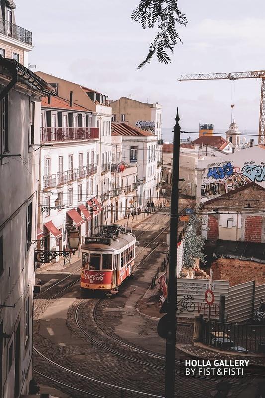 Трамвай на узкой улице в Лиссабоне на фоне граффити.
