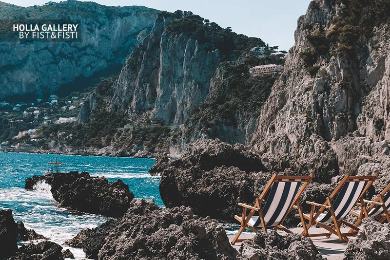 Пляж с шезлонгами среди скал в заливе на Капри в Италии