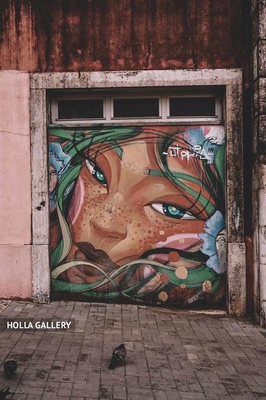 Граффити девушки в листьях с веснушками на стене Лиссабона.