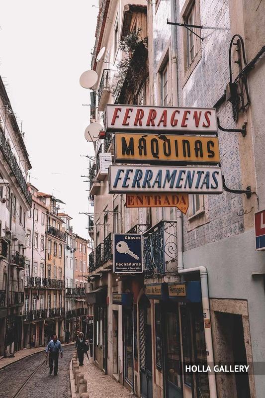 Узкая улочка Лиссабона с вывесками магазинов, фотообои для интерьера.