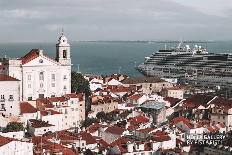 Высокая церковь посреди города Лиссабон на фоне воды и пасмурного неба.
