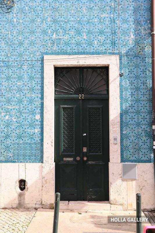 Зеленая дверь в голубой стене в Лиссабоне