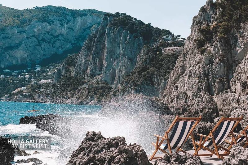 Брызги воды на пляже с шезлонгами среди скал в заливе на Капри в Италии, фото картина