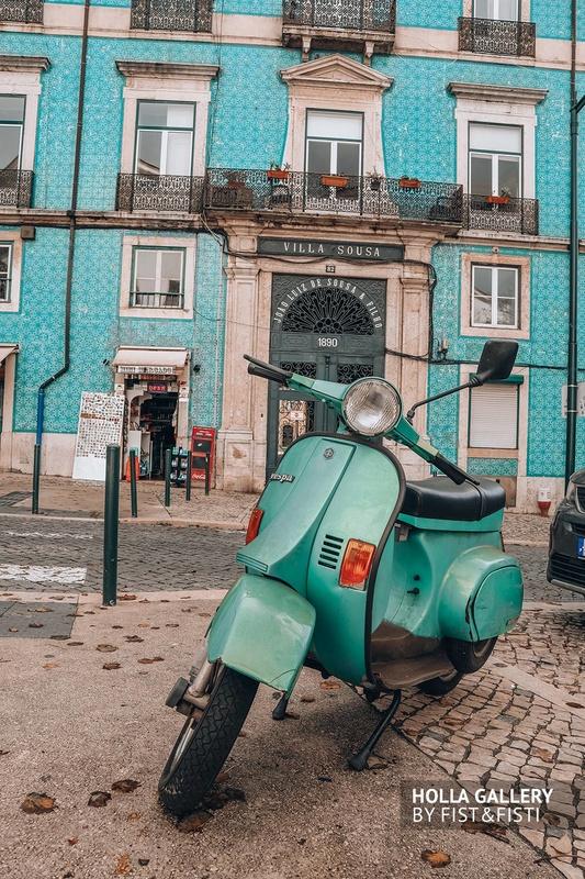 Зеленый мопед посреди улицы в Лиссабоне
