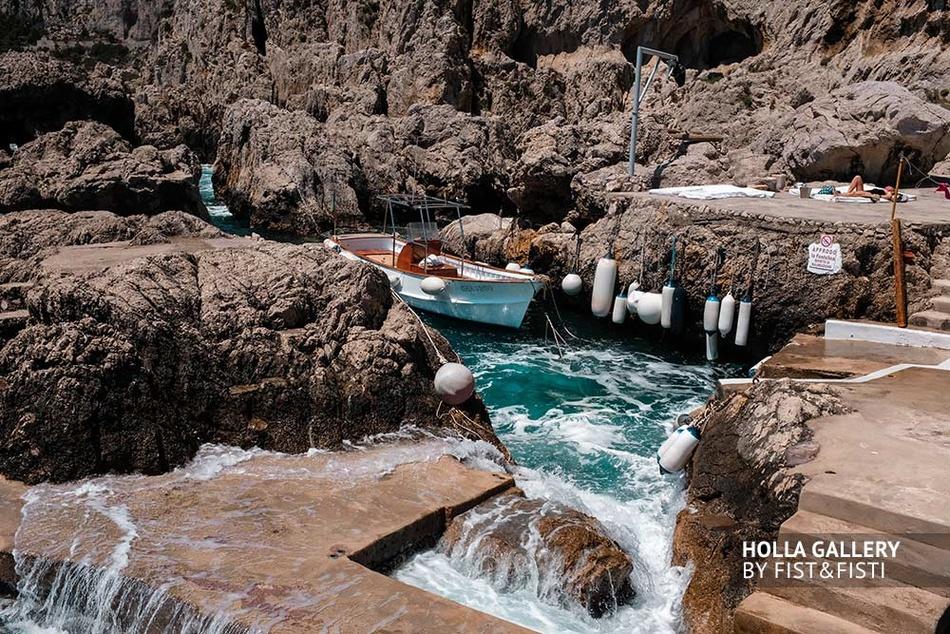 Пришвартованная лодка в узком проливе среди скал на Capri в Италии
