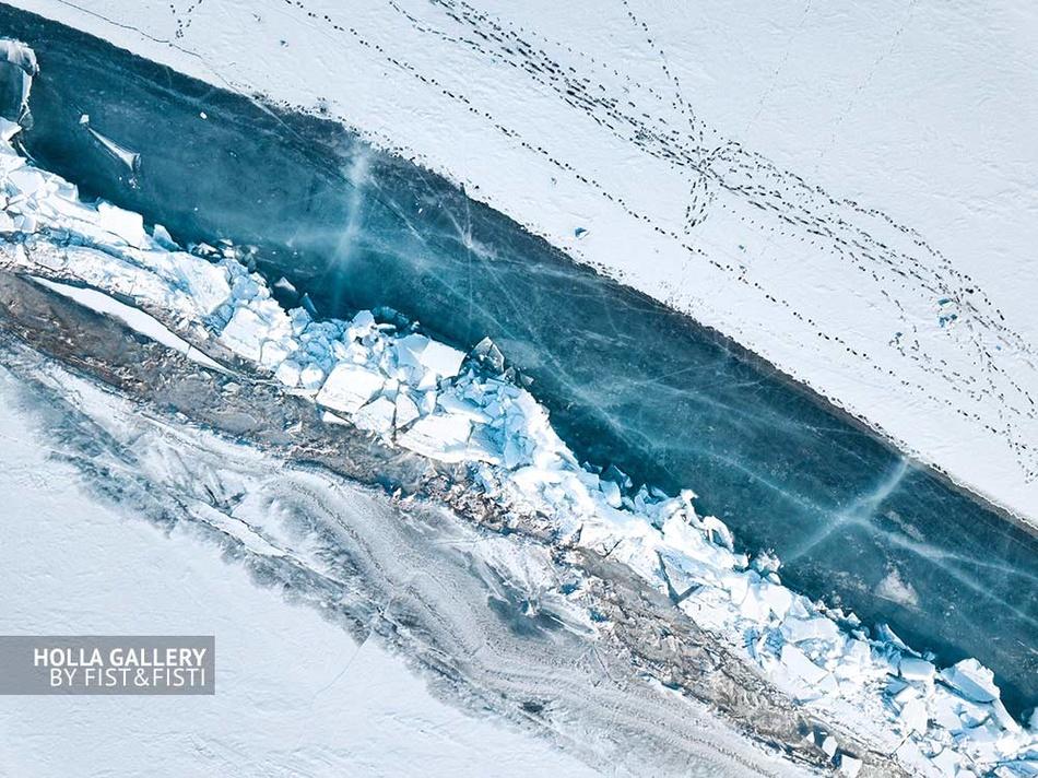 Вид сверху с коптера на побережье замёрзшего Байкала. Озеро во льду и следы человека. Фото для интерьера