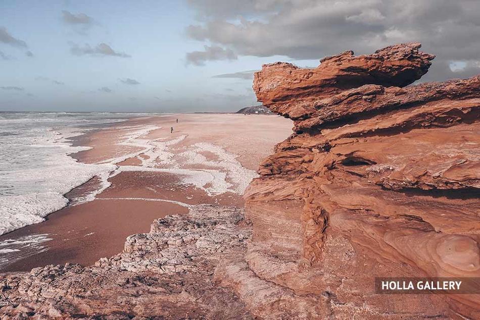 Пляж Назаре с глыбами камней на фоне облаков.