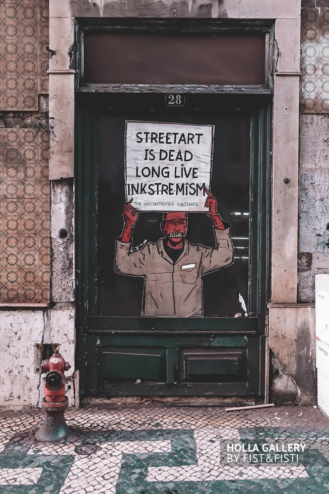 Граффити на двери на улочках Лиссабона.