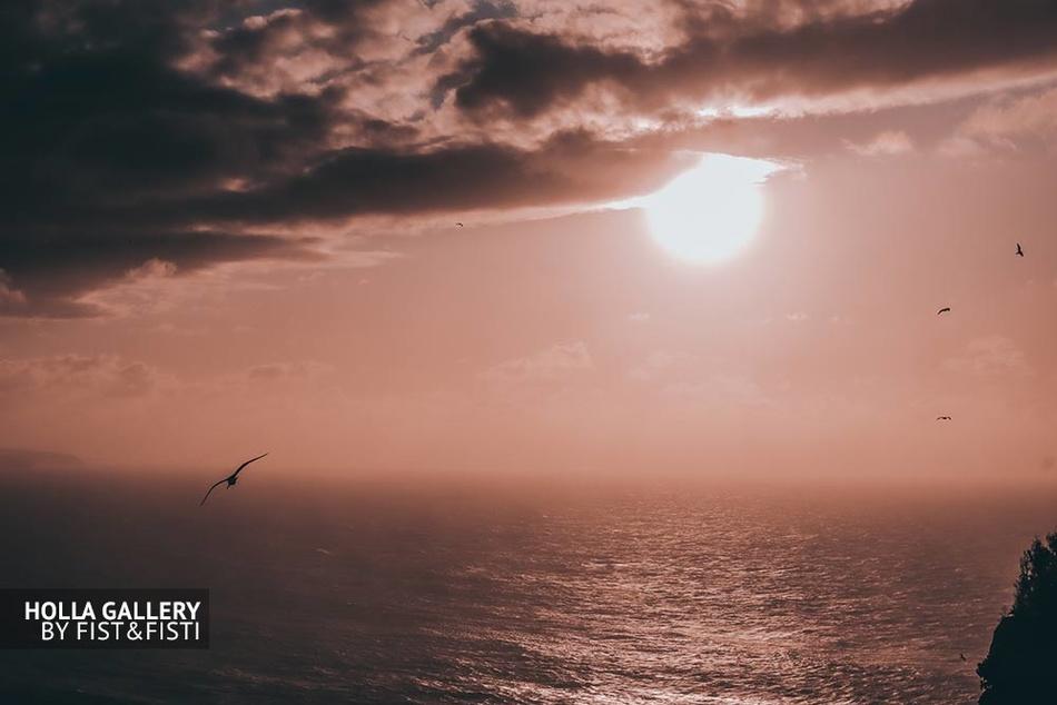 Закат в небе на фоне океана Назаре.