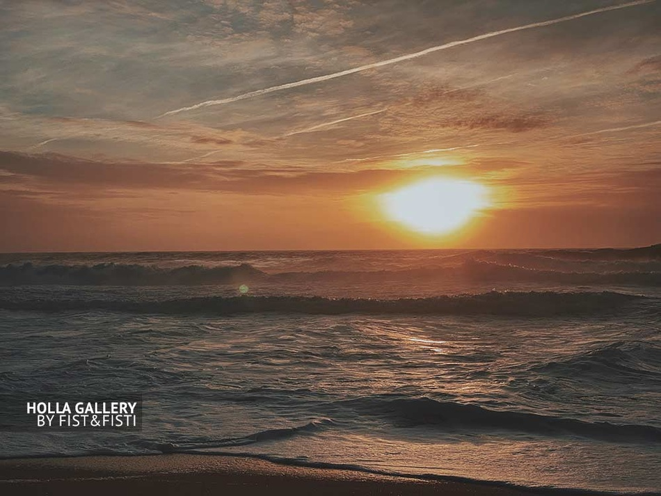 Прибрежные волны на закате у мыса Назаре в Португалии. Облака и следы от самолета
