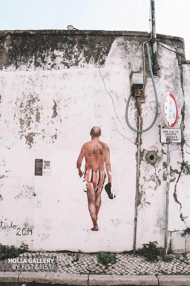 Рисунок идущего мужчины на белой старой стене в Лиссабоне.