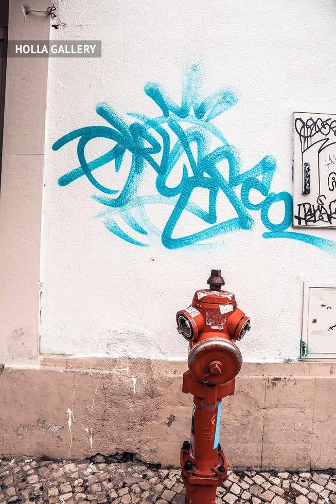 Гидрант у стены с граффити в Лиссабоне