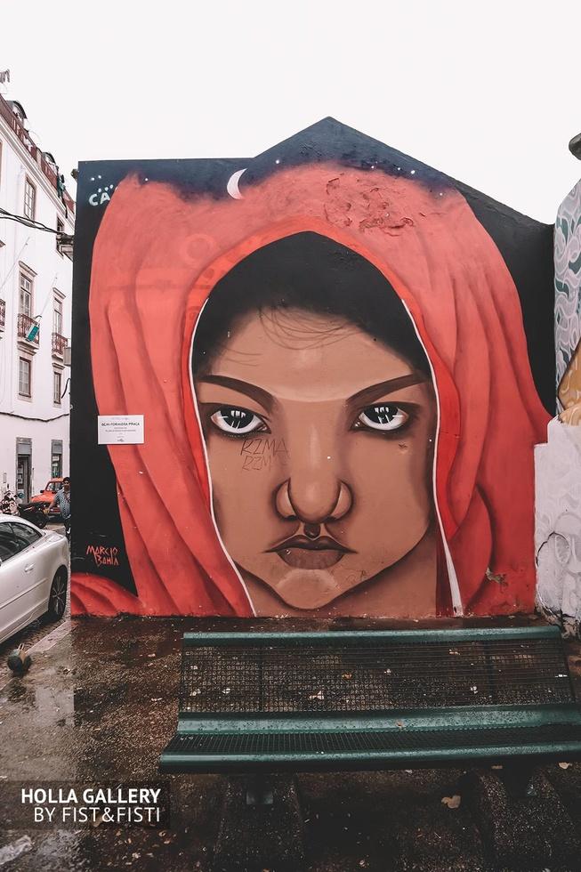 Большое граффити девушки в капюшоне на стене Лиссабона.