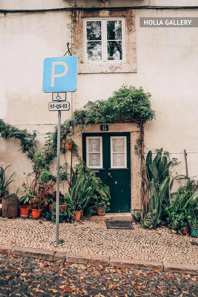 Заросшая дверь дома и знак парков в Лиссабоне