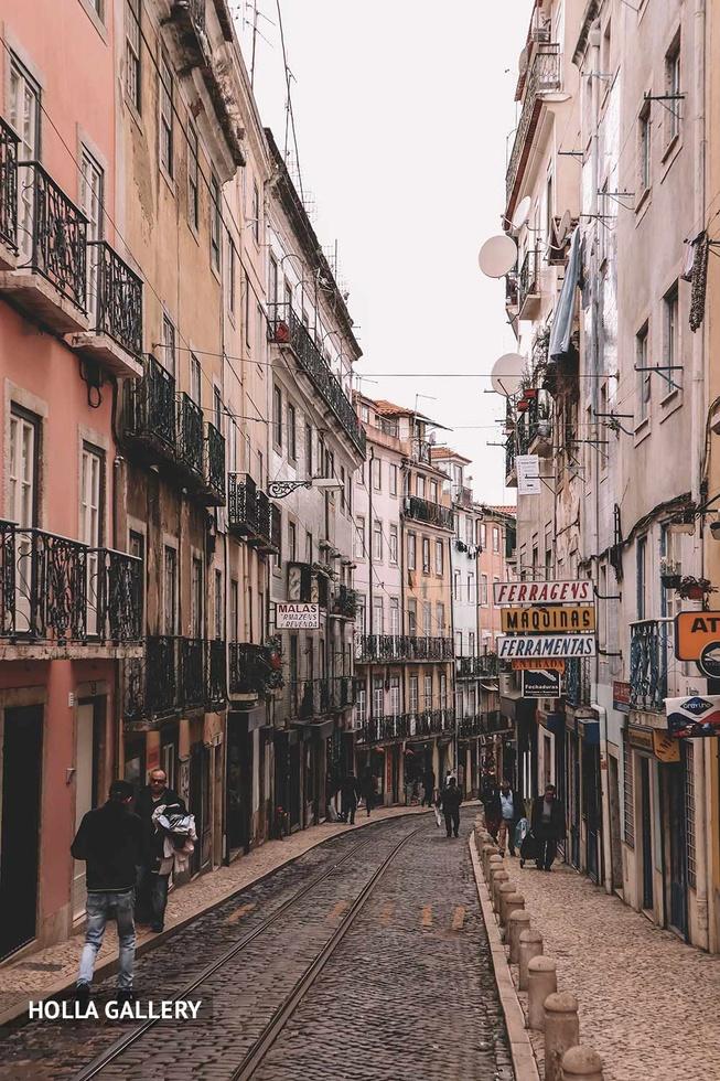 Узкая улица с трамвайными путями в Лиссабоне