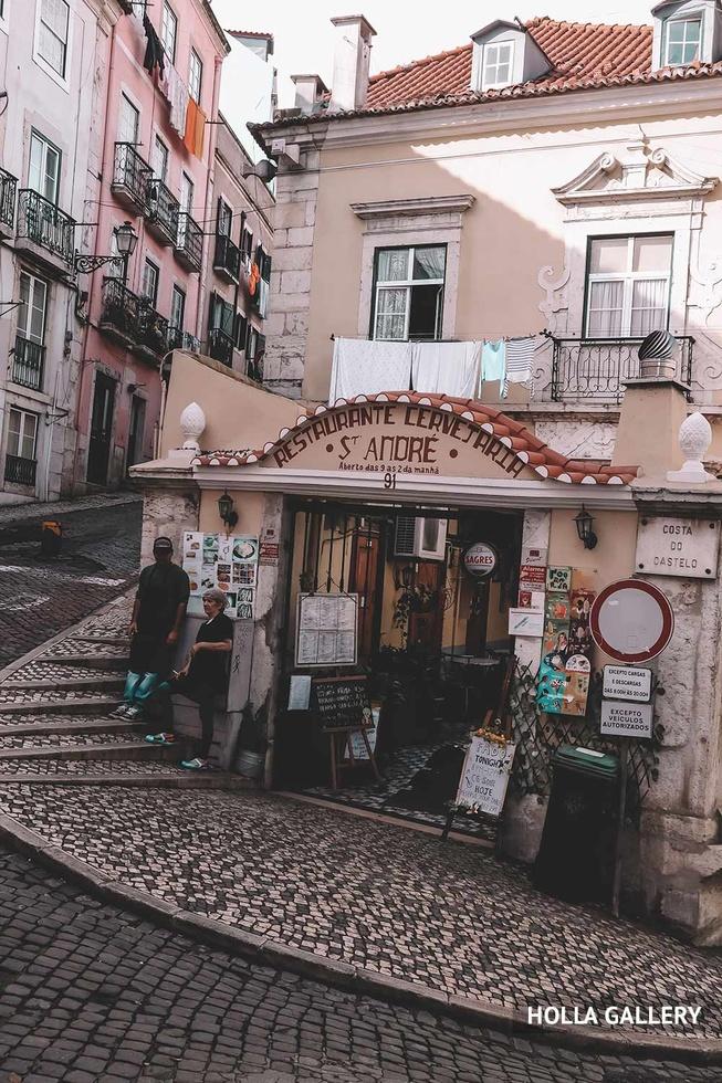 Поворачивающая улица с магазином в Лиссабоне