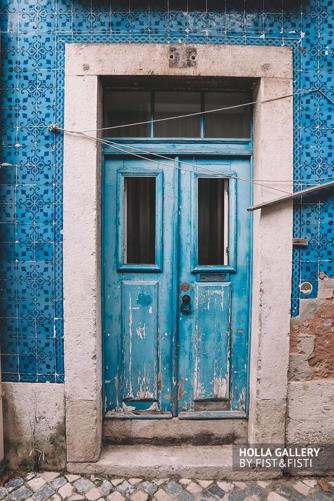 Узкая деревянная дверь в стене на улице Лиссабона. Фотообои для интерьера Лиссабон.