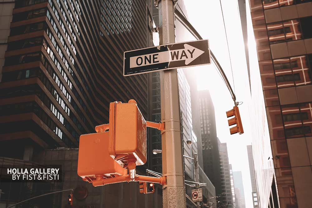 Дорожный знак One Way на светофоре перекрестка в Нью-Йорке среди небоскребов, фото картина. Мегаполис
