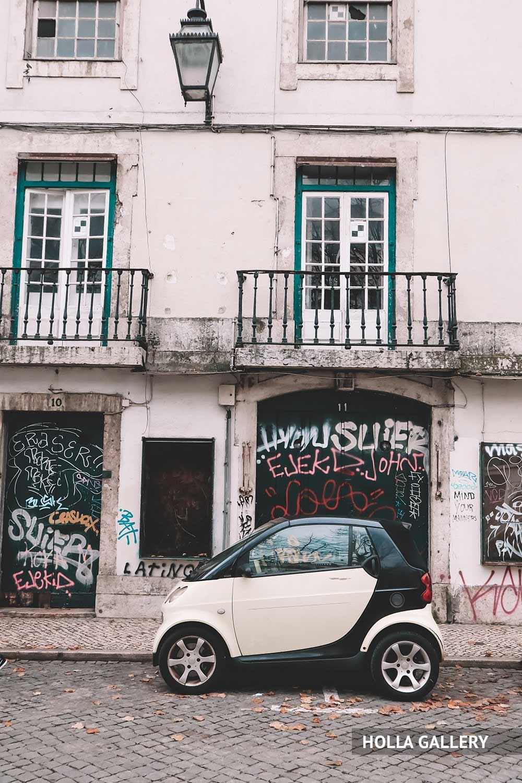 Белая машина у стены с граффити в Лиссабоне