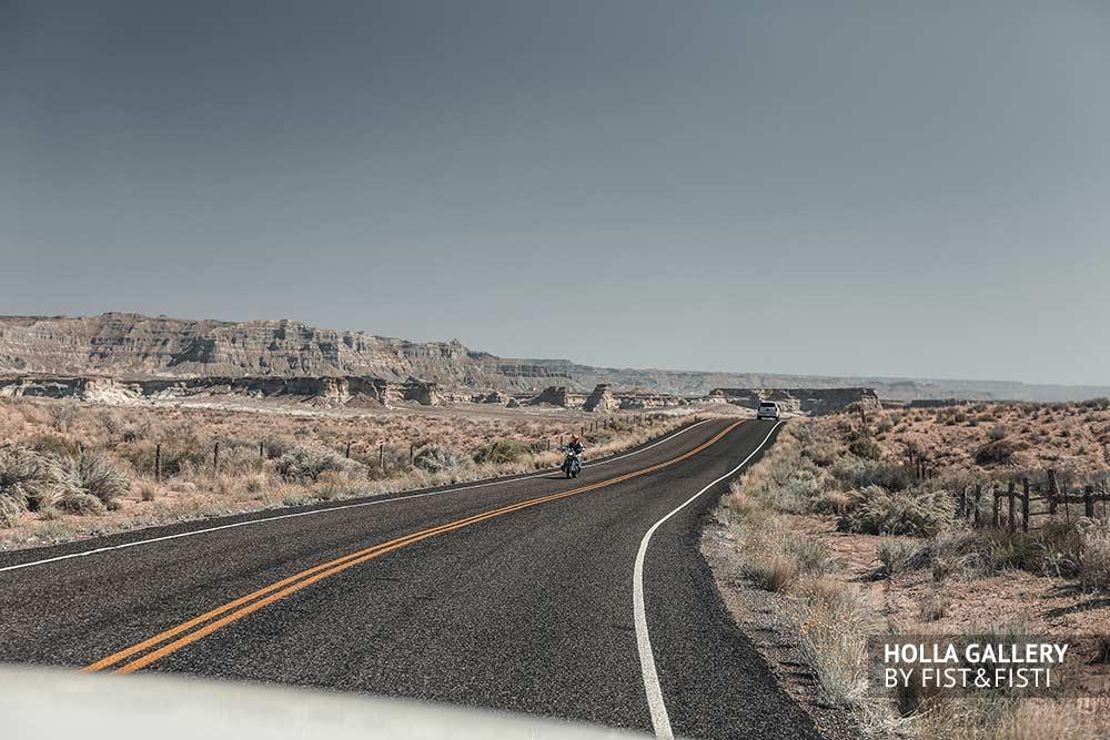 Мотоцикл и автомобиль на дороге посреди пустыни в Utah. Автострада в США