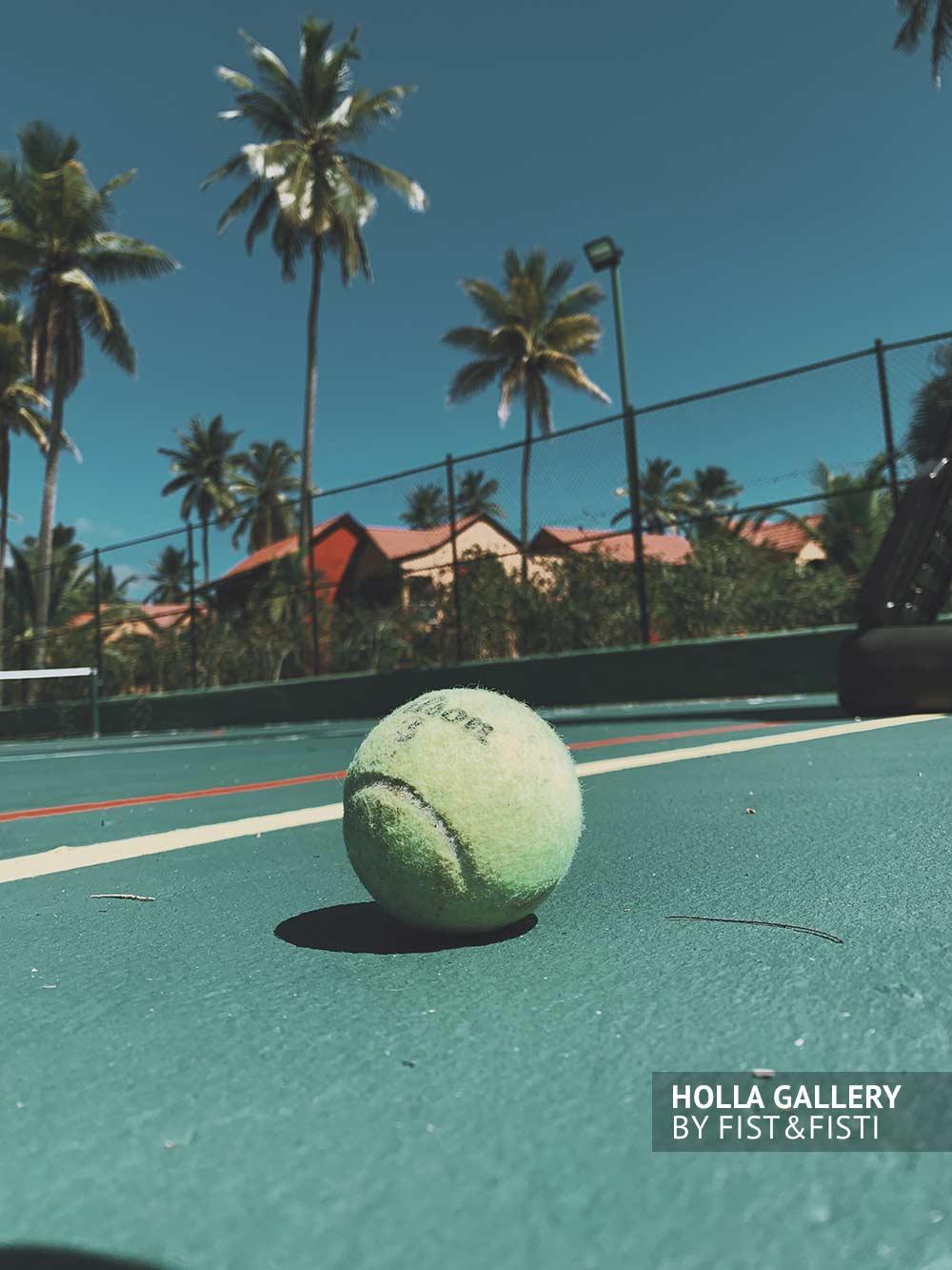 Мяч на теннисном корте на фоне коттеджей и высоких пальм Доминиканской Республики