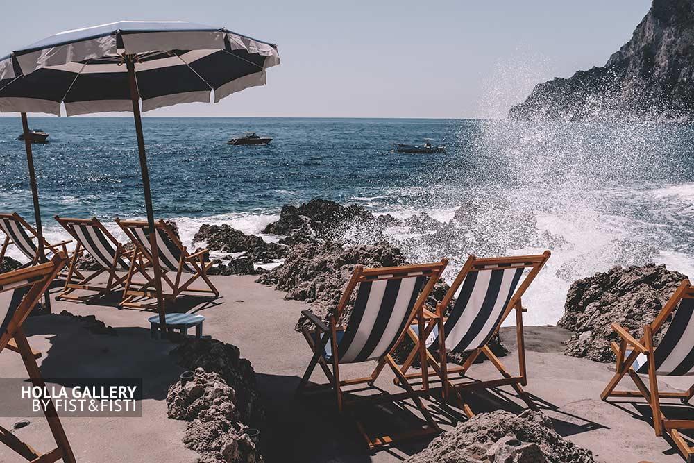 Брызги волн у каменистого пляжа с шезлонгами на Capri. На фоне лодки в заливе. Фото для интерьера