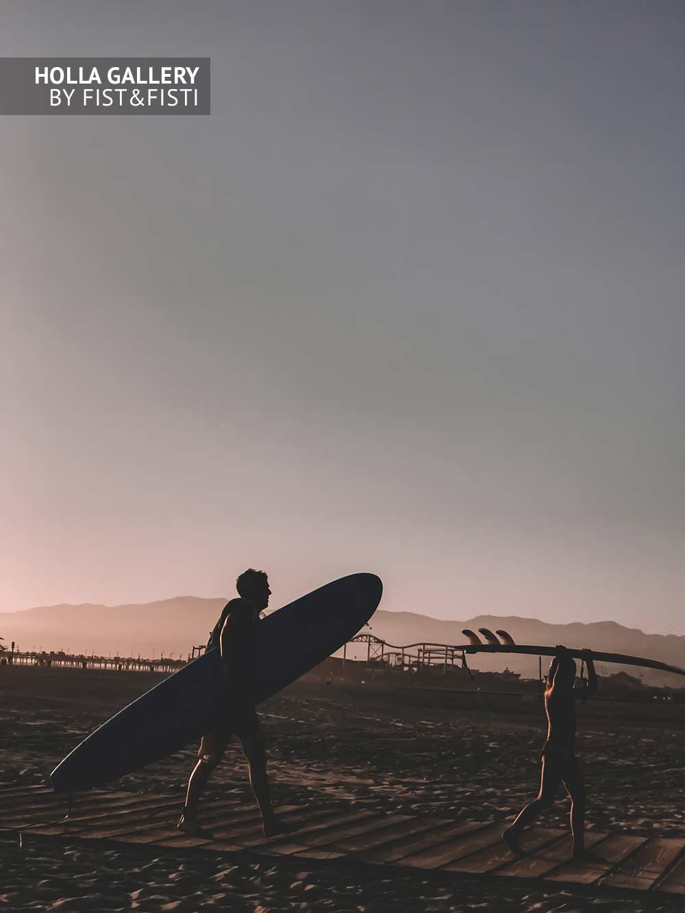Серферы на пляже в Санта-Монике с досками в руках. Ясное небо и горы на фоне
