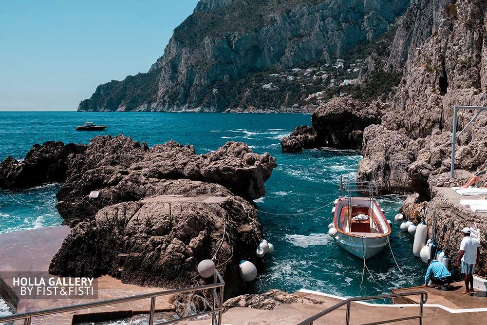 Залив среди скал на побережье Carpi, Италия. Лодка и яхта в заливе