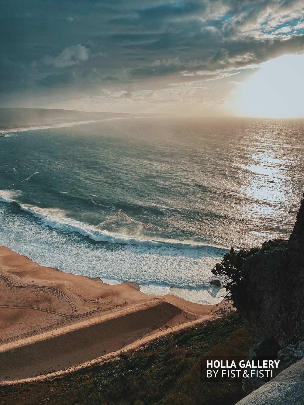 Панорамный вид на бухту у мыса Назаре. Португалия. Волны на закате