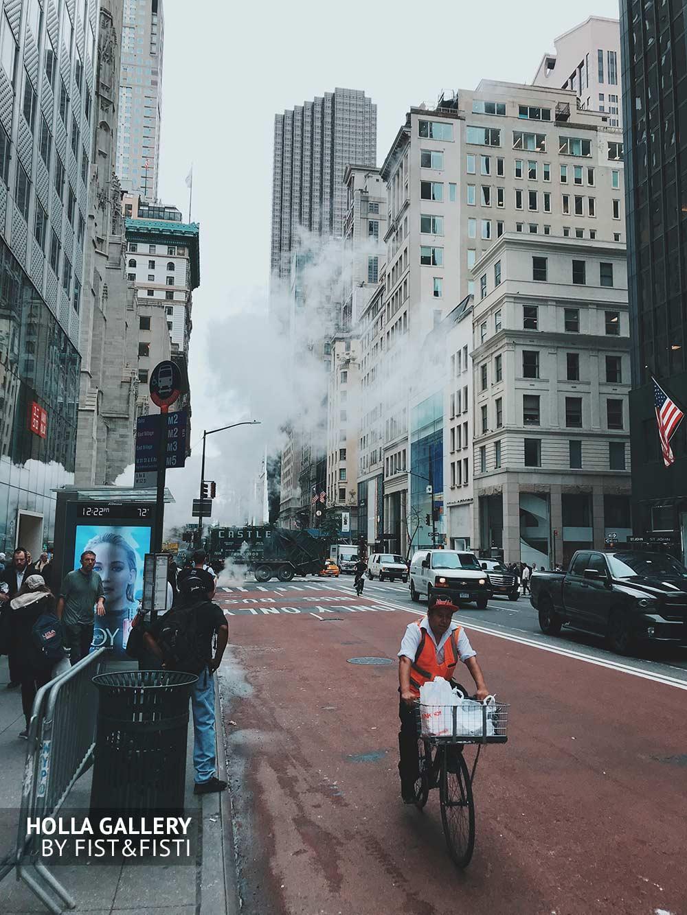 Рабочий на велосипеде едет по улице Нью-Йорка среди небоскребов. Фотогалерея
