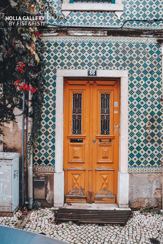 Красивая деревянная желтая дверь в архитектуре Лиссабона.