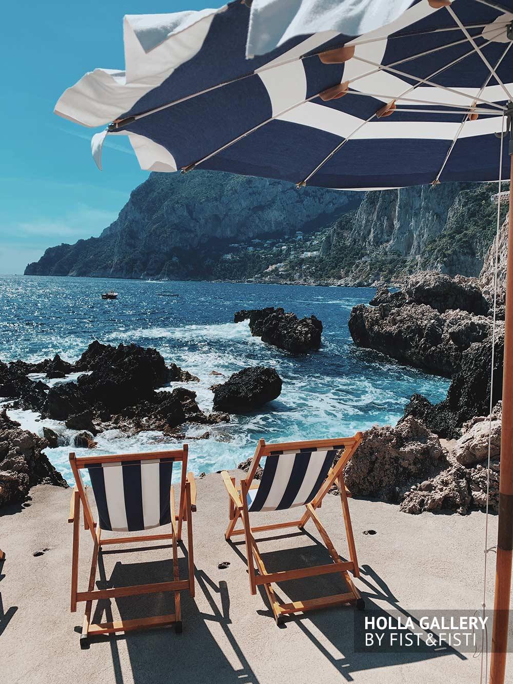 Скалистый пляж на Капри с шезлонгами. Фото для интерьера